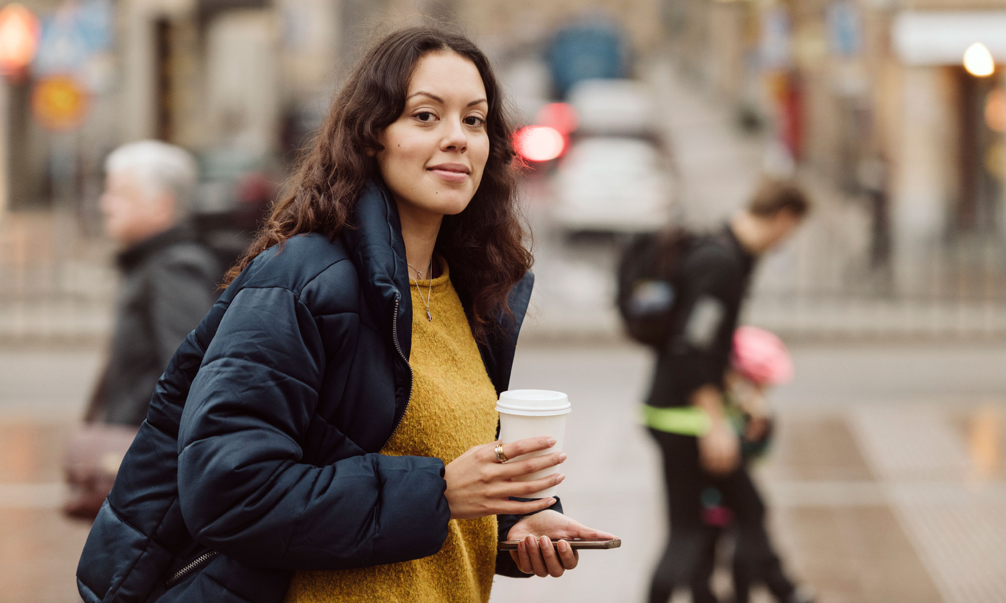 Woman in the city holding a coffee mug.