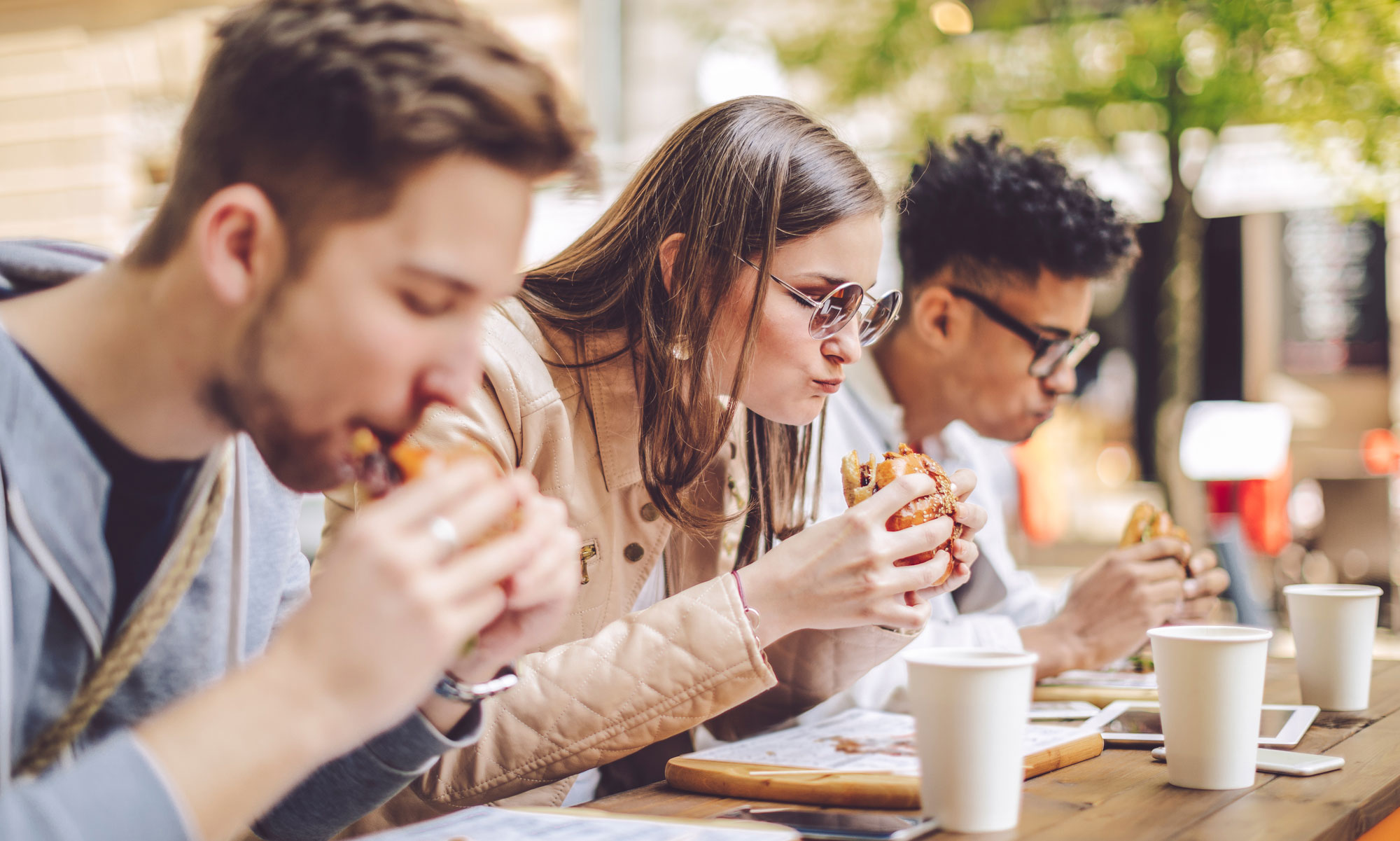 Three young people eating burgers.